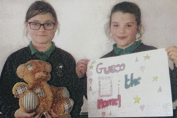 Two girls holding a teddy bear and a sign